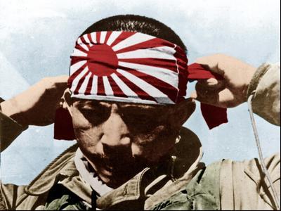 Японский камикадзе надевает на лоб повязку с восходящим солнцем